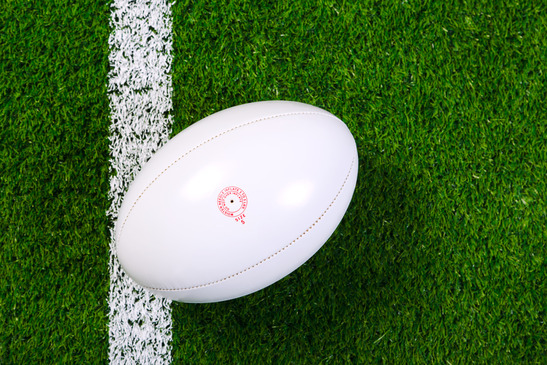 Rugby ball on artificial grass from above.